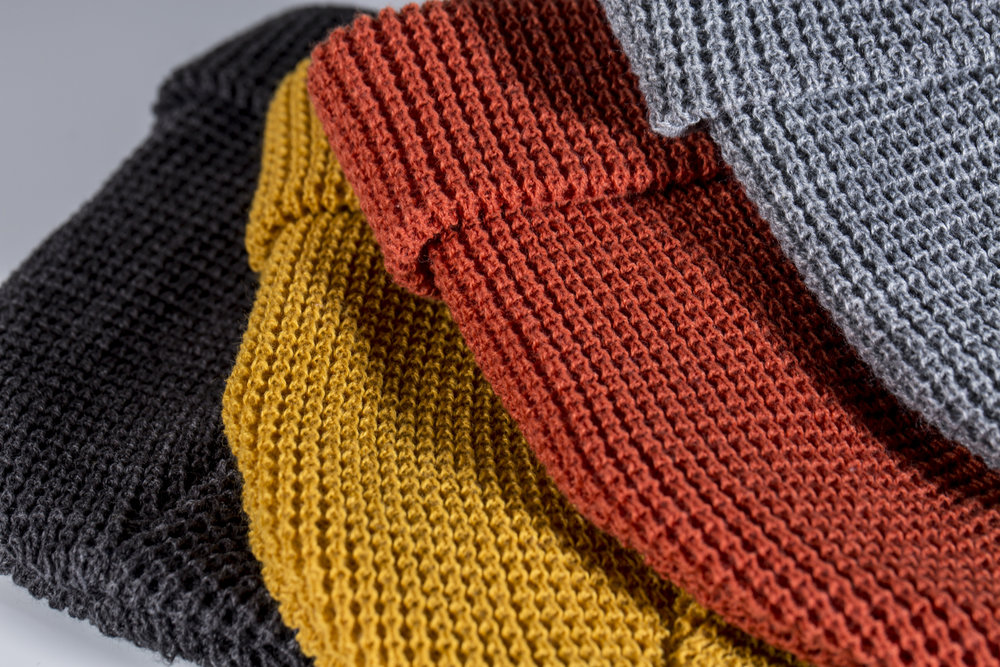 A heather charcoal wheat and rust waffle knit folded beanies showing thread detail